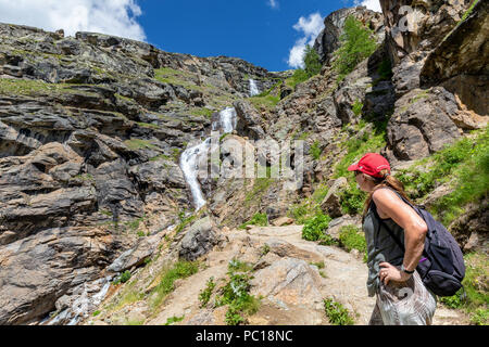 Female hiker looking at a waterfall in Valsavarenche, Aosta Valley, Valle d'Aosta, Italy - Stock Photo