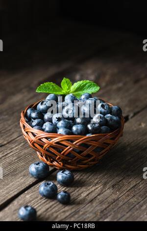 Blueberries in basket on wooden table. Freshly picked blueberries. Low key, dark food photo. Summer harvest. Selective focus - Stock Photo