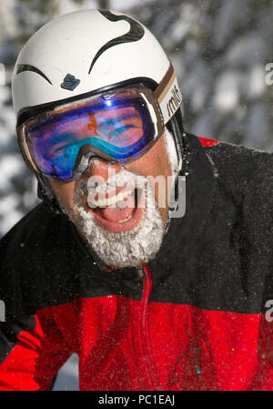 Happy skier face covered in snow after a fresh powder day at Lake Tahoe Ski resorts. - Stock Photo