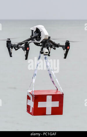 A DJI Inspire drone demonstrates how it can deliver a box of first aid supplies to a remote site quickly. - Stock Photo