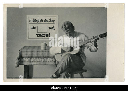 German historical photo postcard: soldier in forage cap plays guitar sitting on a chair. The army's leisure, world war two, Germany, Third Reich - Stock Photo