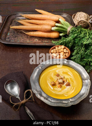 Tasty vegetarian carrot soup served with cream croutons in metal pewter bowl. Bunch of carrots, croutons and spoon on dark brown background - Stock Photo