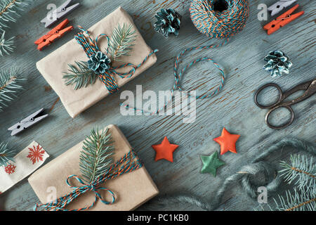Rustic wooden background in green and orange with fir branches and Christmas gifts in simple brown wrapping paper. Seasonal background shot from above - Stock Photo