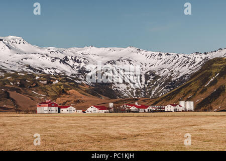 Typical Icelandic landscape with white houses red roof against mountains in small village in South Iceland. - Stock Photo