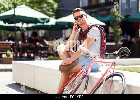 Handsome young hipster man sitting near the bicycle and using smartphone in the sunny street - Stock Photo