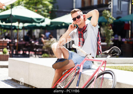 Handsome young hipster man in sunglasses sitting near the bicycle and using smartphone in the sunny street - Stock Photo