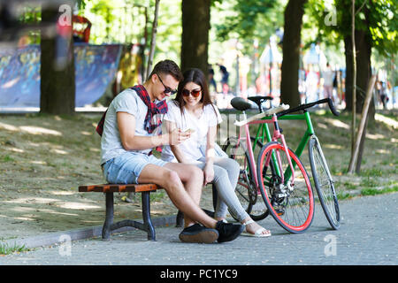 Young couple in love with bicycle sitting on beanch and looking something in the smartphone in the sunny summer park - Stock Photo