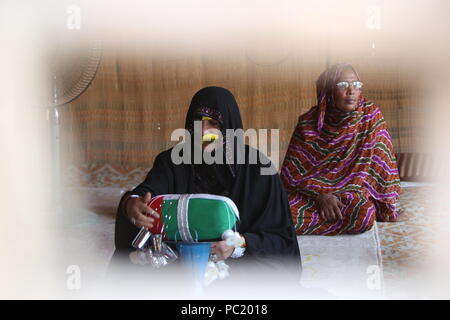 A woman sporting a metallic burqa knits Emirati flag in the heritage village in Fujairah. The village is place to items showing Emirati culture. - Stock Photo