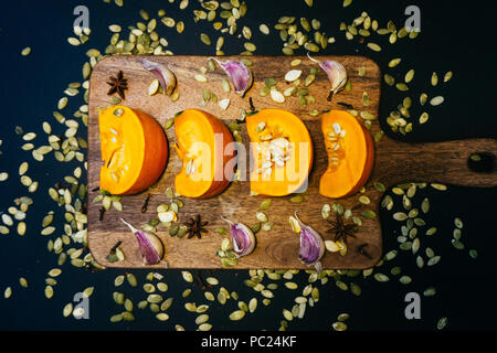Sliced fresh pumpkin on a wooden board with spices and pumpkin seeds. Autumn mood. - Stock Photo