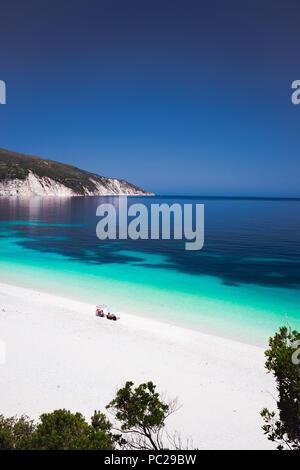 Fteri beach Kefalonia, Greece. Family under umbrella on pebble beach. Clear blue azure emerald sea water in lagoon. White rocks in background - Stock Photo