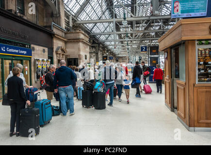 Passengers queueing to board a Virgin train from Platform 1 in Glasgow Central Station. Train travel, rolling luggage, standing, waiting in line - Stock Photo