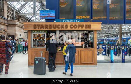 Baristas and customers at the Starbucks outlet in Glasgow Central Station. Passengers queuing for train. Departures board. Ticket barriers. - Stock Photo