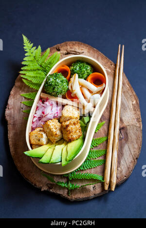 Japanese bento box lunch withg mushrooms, onigiri and tofu - Stock Photo