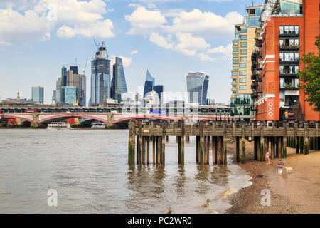 Panoramic view of Oxo Tower Wharf and wooden jetty, Blackfriars Bridge and iconic City of London skyscrapers on the skyline over the River Thames
