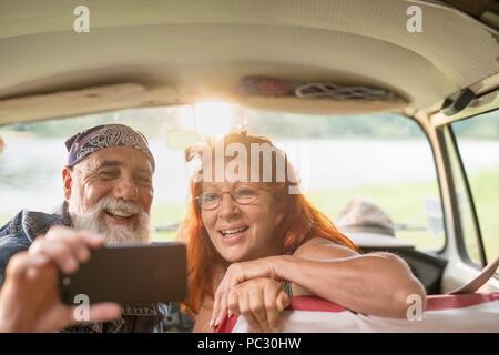 old hipster couple sitting in a car doing a selfie with a phone - Stock Photo
