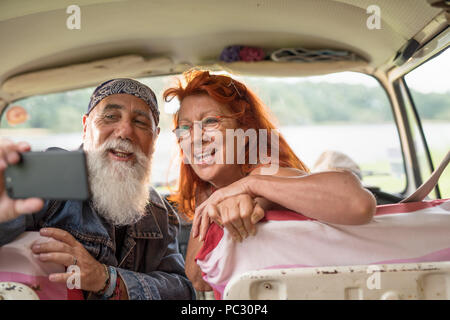 old hipster couple sitting in a van doing a selfie with a phone - Stock Photo