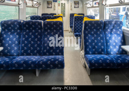 Interior of a Scotrail train carriage while stationary at Glasgow Central station, with passengers and another train seen outside the windows. - Stock Photo
