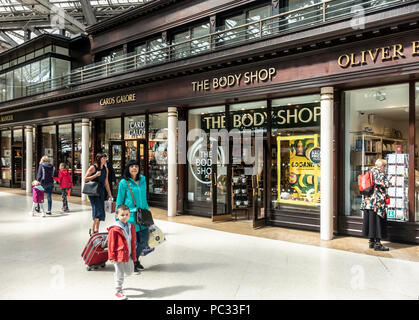 Passengers walking through the concourse of Glasgow Central Station past retail units like The Body Shop, Cards Galore, Oliver Bonas and Pret a Mange - Stock Photo