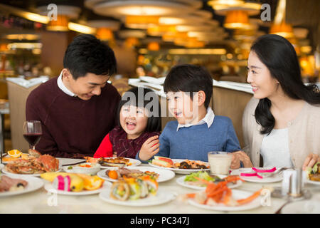 Cheerful young Chinese family having buffet dinner - Stock Photo