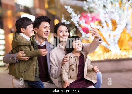 Cheerful young Chinese family taking self portrait with smart phone - Stock Photo