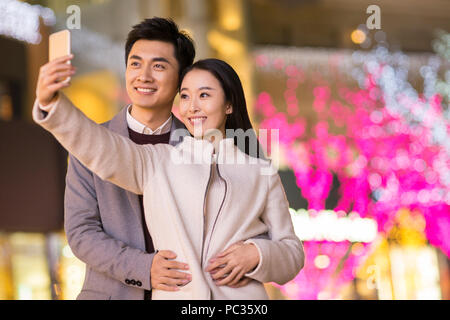 Cheerful young Chinese couple taking self portrait with smart phone - Stock Photo