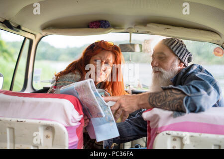 Old hipster couple sitting in a car and looking at a road map  - Stock Photo