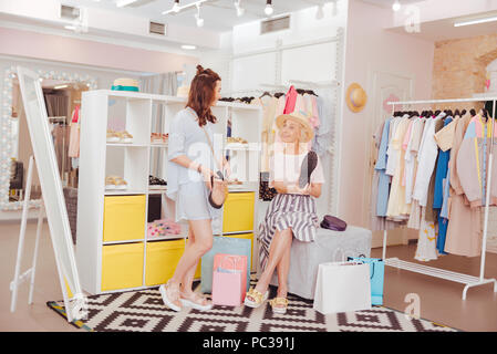In shop together. Loving fashionable mother and daughter spending their time in shop together - Stock Photo