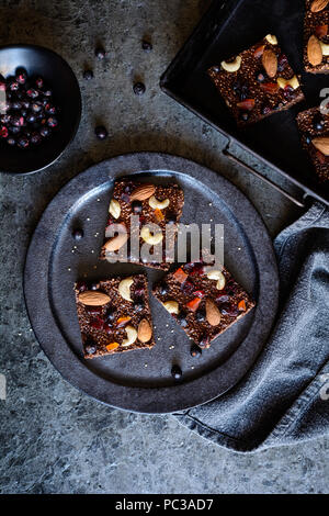 No bake chocolate puffed quinoa bars with freeze dried black currant, candied papaya, cashew nuts, almonds and cranberries - Stock Photo