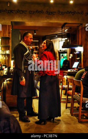 Ukrainian woman talking to the Georgian man in Circasian coat in Georgian restaurant in Dnepropetrovsk (Dnepr) in Ukraine seeking attention and advise - Stock Photo