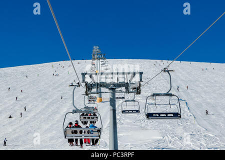 Skiers on a ski lift.Beautiful day on the snow, on ski slope. Piste name is Platoto. - Stock Photo
