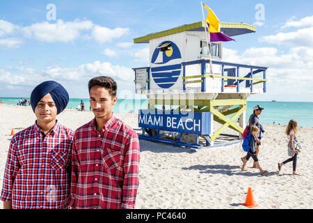 Miami Beach Florida Indians Asian Punjabis Sikh Sikhs educational student trip boy teen young adult turban dastaar lifeguard tower plaid shirt friends - Stock Photo