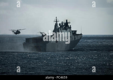 180729-M-QH615-0017 MARINE CORPS BASE HAWAII (July 29, 2018) Two CH-53E Super Stallion helicopters assigned to Marine Heavy Helicopter Squadron 463 (HMH-463) land aboard the Royal Australian Navy landing helicopter dock ship HMAS Adelaide (L01) during an amphibious landing demonstration as part of Rim of the Pacific (RIMPAC) exercise at Pyramid Rock Beach on Marine Corps Base Hawaii July 29, 2018. RIMPAC provides high-value training for task-organized, highly capable Marine Air-Ground Task Force and enhances the critical crisis response capability of U.S. Marines in the Pacific. Twenty-five na - Stock Photo