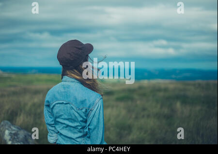 A young woman wearing a baseball cap is standing on a hilltop - Stock Photo