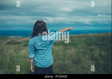 A young woman is standing on a hilltop and is pointing - Stock Photo