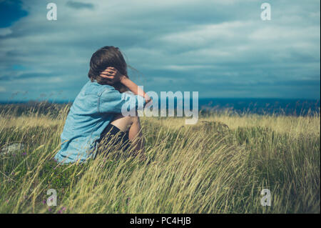 A sad woman is sitting in a field on a windy day - Stock Photo