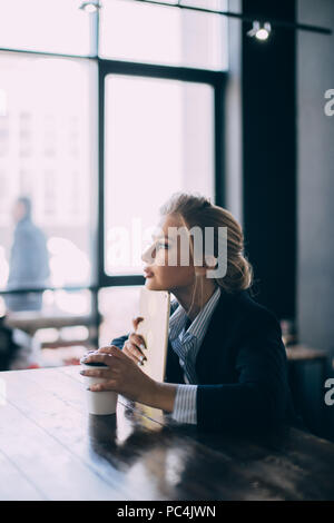 good-looking blond girl is leaning on her tablet and thinking about future plans at the cafe - Stock Photo