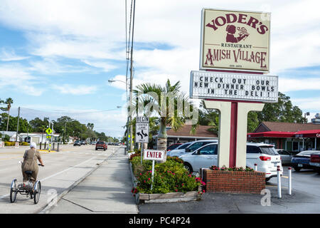 Sarasota Florida Pinecraft Pine Craft Yoder's Amish Village Amish Mennonite snowbird community restaurant sign street traffic woman riding adult tricy - Stock Photo