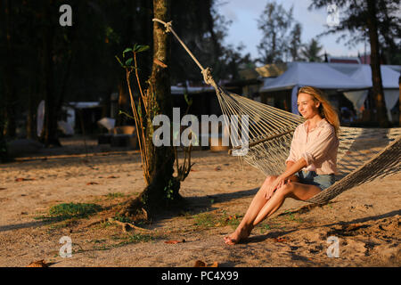 Young caucasian barefoot woman resting on sand in white wicker hammock. - Stock Photo