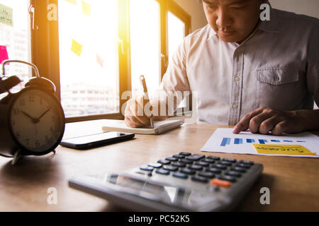 Accountant calculate finance of annual profit by press calculator and summed up balance money by writing on note book in office - Stock Photo