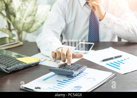 businessman writing and memory on notebook and press on calculator on table, accountant and business concept - Stock Photo