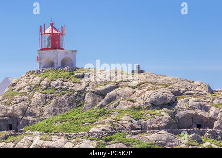 The Lindesnes lighthouse on its foundation with the former fortifications - Stock Photo