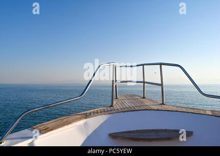 View from yacht over the ocean, horizon in background, blue sky - Stock Photo