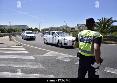A local policeman looks at a taxi rally to protest in Palma de Mallorca, Majorca island, Spain, 31 July 2018, Spain. Taxi drivers in several Spanish cities have joined colleagues in Barcelona, who started the protests last 25 July, to show their support for a taxi strike in defense of the regulation which provides one local license for VTC (Tourism Vehicles with Driver) vehicle, from companies like Uber o Cabify, out of each 30 licenses for taxis. EFE/Atienza - Stock Photo