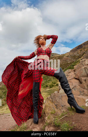 Edinburgh, UK. 31st July 2018. Gingzilla: Glamonster Vs The World. 7ft ginger bearded bombshell drag queen with the longest legs, towering by Arthur's Seat - angles to make her look as big as the hill Credit: Andrew Eaton/Alamy Live News. - Stock Photo