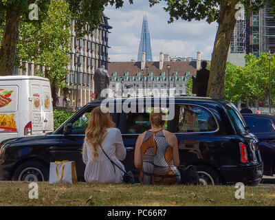 Westminster. London. UK 31 July 2018 - Two women sitting  on Parliament Square with a view of The Shard on a sunny but fresher day in the capital. According to The Met Office the heatwave is to return after a brief drop in temperature and rainfall in the UK.  32 degrees celsius is forecasted for the coming weekend.   Credit: Dinendra Haria/Alamy Live News - Stock Photo