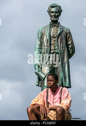 Edinburgh Fringe Festival, Henry Box Brown: Musical Journey photocall, 1st August 2018. Edinburgh, Scotland, UK. The cast at Abraham Lincoln Memorial, Old Calton Burial Ground, which commemorates Scots who fought with the Union in American Civil War. Tony Award winner Ben Harney and writer Mehr Mansuri create the musical about a 1850s Virginia slave. A young Black American boy sits at the foot of a statue of  Abraham Lincoln - Stock Photo