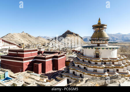 Gyantse Kumbum in Pelkor Chode or Palcho monastery with Gyantse Dzong or fort in the background, Tibet - Stock Photo