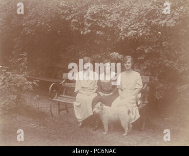 Vintage Photograph of Three Ladies Sat on a Bench With Their Dog in The Garden at Forest Hill. - Stock Photo