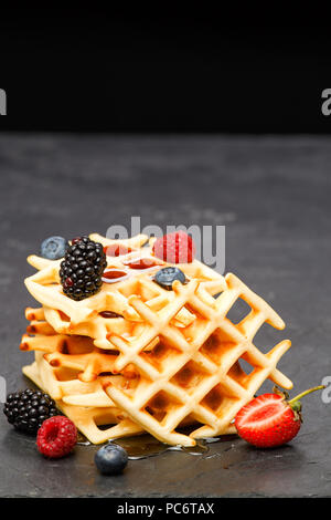 Photo of viennese wafers with berries pouring honey on black background - Stock Photo
