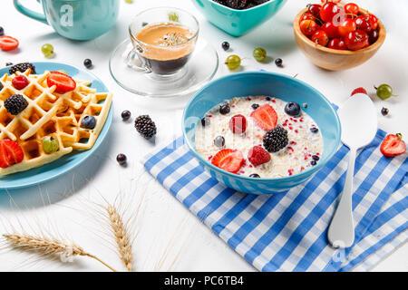 Photo of Viennese waffles, oatmeal, coffee, fresh raspberries, strawberries, gooseberries - Stock Photo